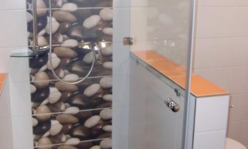 Modernes Badezimmer weiß gefliest, aufgelockert mit farbigen, orangen und schwarzen Fliesen, Duschkabine mit dekorativen Steinen